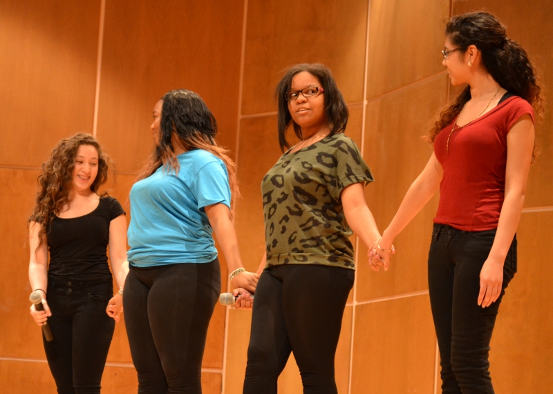 """May 2014 -- NHS students Leslie Benavides (black), Mariyama Camara (blue), Alexis Scott (green) and Liliana Chavez (red) perform in """"We Become So Numb,"""" focusing on how hurtful words become desensitized."""