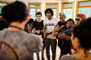 Jonathan Tucker, DC Youth Poetry Slam Team's Youth Programs Coordinator (foreground), leads Writers' House students and slam team members alike in an icebreaker game of Ninja. (Charles Mitchell/Bloc Photographer)