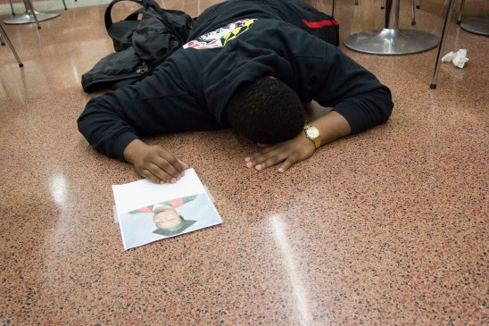 Alumnus Damien Pinkett reenacts the Michael Brown scene, lying still for the majority of the protest. (Trey Sherman/Bloc Reporter)