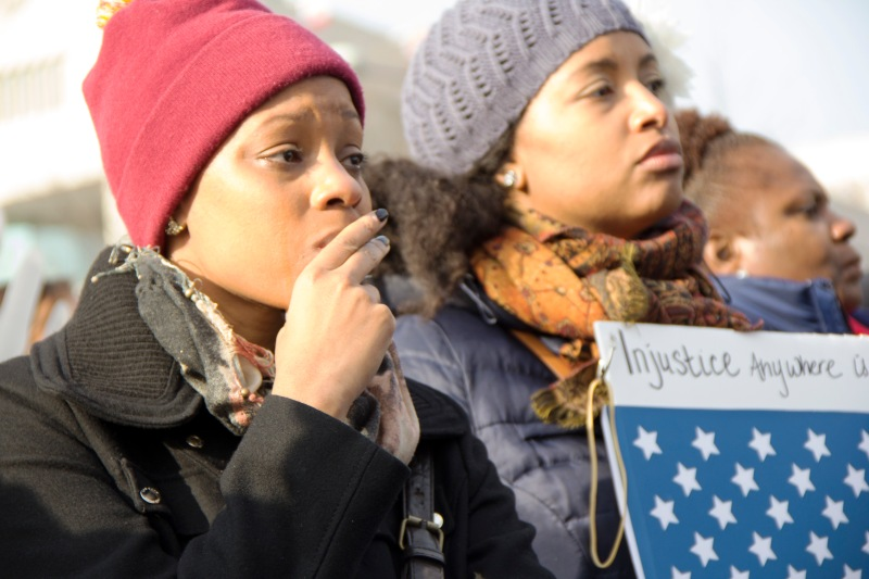 Ajoia Wescott (left) and Shelley Barnes listen as Eric Garner's loved ones speak. (Trey Sherman/Bloc Reporter)