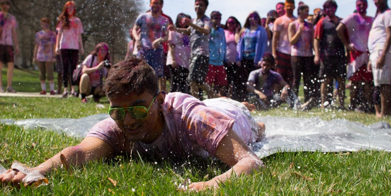 "Students clean the ""gulal"" from their skin by diving across a makeshift slip-n-slide. (Ryan Eskalis/For The Bloc)"