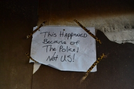 An anonymous sign is taped to the ruins of a CVS destroyed in Baltimore Monday night. (Aiyah Sibay/Bloc Reporter)