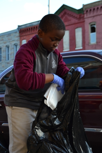 A boy helps pick up trash off of the Baltimore streets in the aftermath of Monday's riots.
