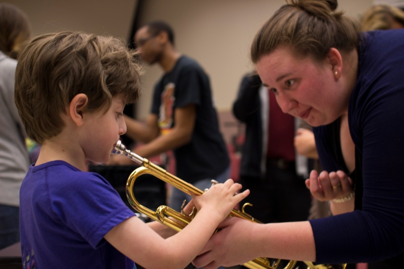Grant Ewing (left) receives instructions on how to play a trumpet from Hannah Moock (right), a junior music education major. Children explore and experiment with orchestral instruments at the Instrument Petting Zoo event. (Ryan Eskalis/Bloc Photographer)