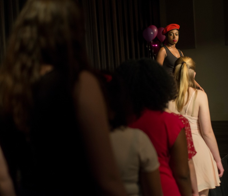 """Tatiana Taylor performs """"My Angry Vagina."""" She impersonates a drill instructor who is furious about the mistreatment of her vagina. Her fellow cast members stomped in cadence with her as they approached the stage. (Ryan Eskalis/Bloc Reporter)"""