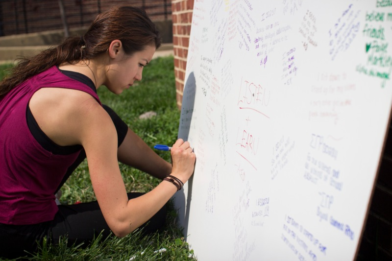 "Sophomore environmental policy major Erin Saunders adds her response to the ""What Do You SD2SU For?"" board. The board consists of pledges made by UMD students vowing to take a stance against sexual violence and assault. (Ryan Eskalis/Bloc Reporter)"