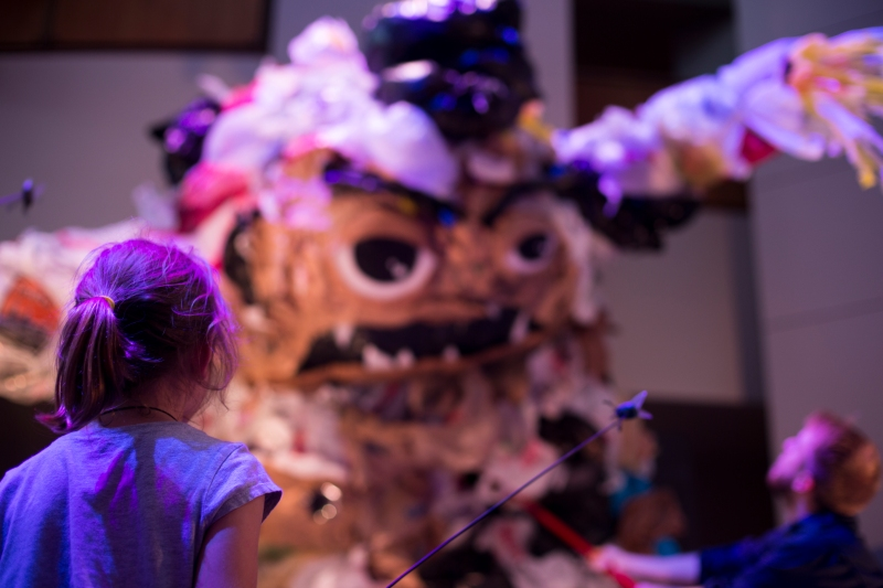 A young girl watches as actors performing as janitors combat the monster that emerges from the dumpster display, Dumpster Monster, at NextNOW Fest. Photo credit: Ryan Eskalis/Bloc Reporter