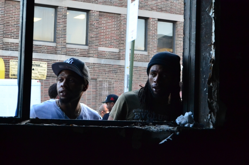 Two men look in through the window of a burned-out CVS. (Aiyah Sibay/ for the Bloc)