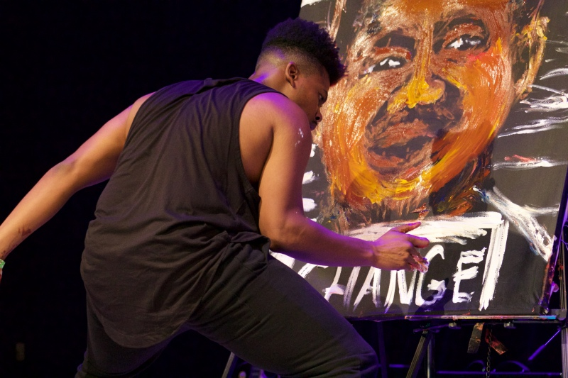 Lionel Daniels finishes his self-portrait, in which he depicts himself behind bars. Many of Daniels' works feature African Americans calling for change in American society, a common theme throughout the event. (Julia Lerner/Bloc Reporter)