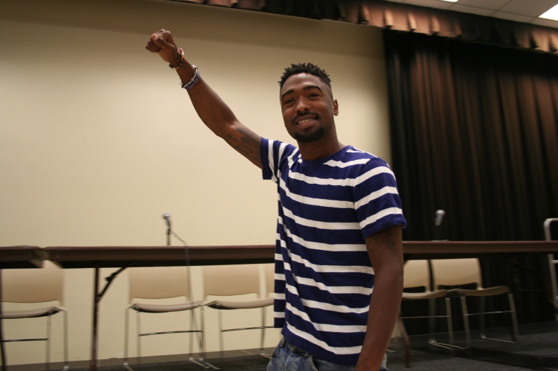 Kondwani Fidel, a Baltimore activist, delivers a poetry performance before the Truth and Solutions in Baltimore panel discussion began. His poetry described his experiences while growing up and living in Baltimore. (Vickie Connor/Bloc Reporter)