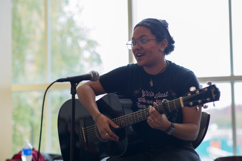 Sam Sauter sings a song in front of the Co-op in stamp during the Queer open mic. (Josh Loock/Bloc Reporter)