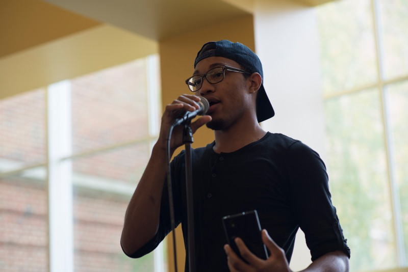 Dre Hawkins recites a poem he wrote about self harm at the Queer open min inside of Stamp. (Josh Loock/Bloc Reporter)