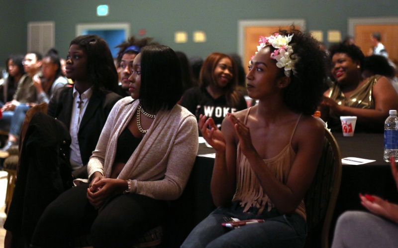 "After modeling in the hair fashion show, flowered Ariana Braganza applauds in the audience during the ""My Black is Beautiful"" event in College Park, Md. on Feb. 25, 2016. (Jack Angelo/Bloc Reporter)"