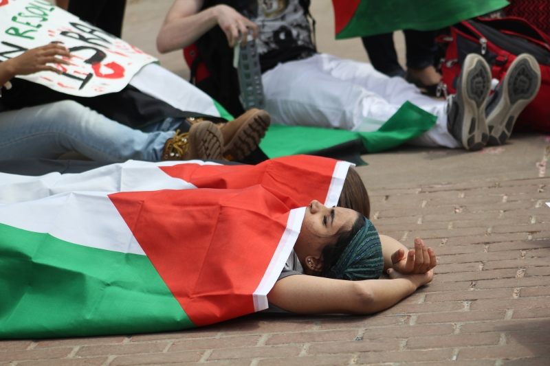 Students protestors lie in the center of Israelfest, an event celebrating Israeli culture. Many covered themselves in Palestinian flags, while others used signs from the protestors. (Photo by Julia Lerner/ Bloc Reporter)