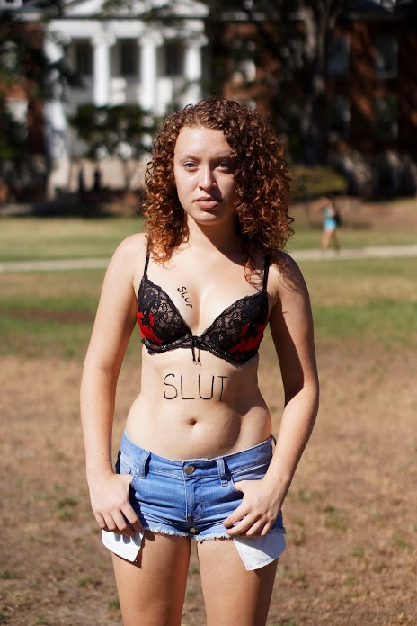 "Sarah Lader, 18, freshman, Family Science major, stands unashamed with ""slut"" labels on her body. (Heather Kim/Bloc Reporter)"