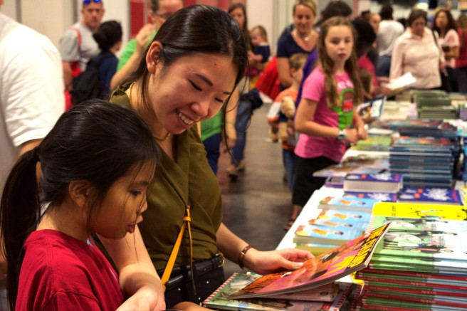 "10-year-old Bella Nguyen from Arlington, Va. reads books from the children's table with her ""bud"" Ruth Tam, 25, a Washington, D.C. resident at the 16th Annual National Book Festival Saturday Sept. 24, 2016. (Jordan Stovka/Bloc Reporter)"