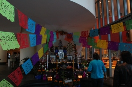 Colorful and intricate papel picado banners hang above an offrenda. (Katrina Schmidt/Bloc Reporter)