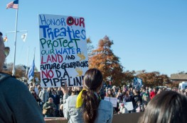 Heather Mendoza held up multiple signs throughout the event to stand in solidarity with other other indigenous peoples. (Cassie Osvatics/Bloc Reporter)