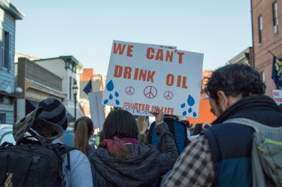 "Attendees at the rally held signs throughout the event to protest the Dakota Access Pipeline. As they march through the streets, the hundreds of supporters chanted ""water is life"" in response to the organizers of the march shouting ""Mni Wiconi"" and ""keep it in the soil"" in response to ""Can't drink oil."" (Cassie Osvatics/Bloc Reporter)"