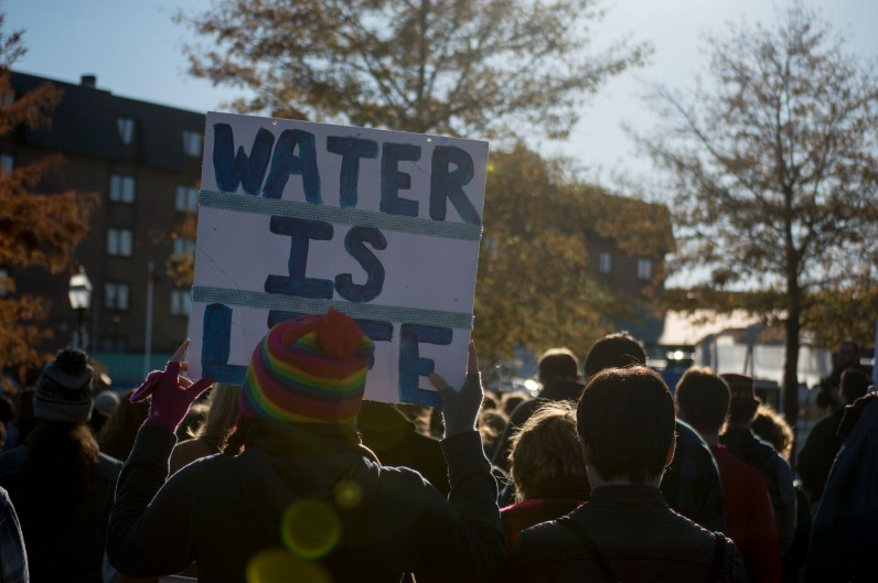 """Attendees at the rally held signs throughout the event to protest the Dakota Access Pipeline. As they march through the streets, the hundreds of supporters chanted """"water is life"""" in response to the organizers of the march shouting """"Mni Wiconi"""" and """"keep it in the soil"""" in response to """"Can't drink oil."""" (Cassie Osvatics/Bloc Reporter)"""