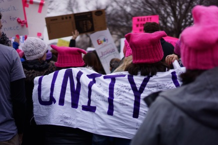 """Protesters march towards the White House with a sign that reads """"UNITY."""" (Heather Kim/Bloc Photographer)"""