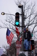 Protester stands on top of a traffic light to look out at the sea of marchers. (Bloc Photographer)
