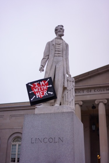 "Lincoln poses with a sign left behind by a protester that reads ""I'M WITH HER."" (Heather Kim/Bloc Photographer)"