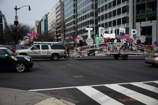 "Thirty minutes after the scheduled meeting time, and after a few attendees expressed anxiety over the march being a hoax, worries were quelled when the ""Trump Unity Bridge"" came rolling down Connecticut Avenue. Marchers were elated to hear the song ""God Bless America"" blasting from the speakers attached to the parade-float-like structure as it approached Farragut square in Washington, D.C. Police officers later temporarily closed down portions of 17th St. NW to make way for the vehicle, as it made its way to the White House. (Josh Loock/Bloc Photographer)"