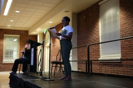Jagjot Kaur, a sophomore who has been doing spoken word for three years now, performs in front of the diverse crowd. (Heather Kim/Bloc Photographer)