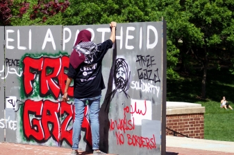 A student examines the wall constructed by the groups boycotting Israelfest. The wall was intended to represent the between Israel and Palestine, and featured similar graffiti messages, definitions and calls for peace. (Julia Lerner/Photography Editor)