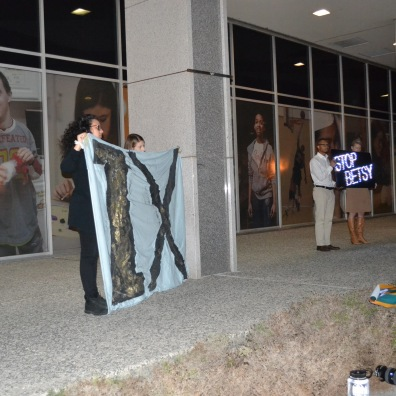 """People hold up a Title IX sign and a """"Stop Betsy"""" sign at the vigil. (Lisa Woolfson/Bloc Photographer)"""
