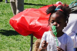 A young girl blows bubbles with her father on McKeldin Mall. (Taneen Momeni/Bloc Reporter)