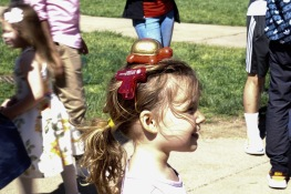 After collecting Testudos from the fountain on McKeldin Mall, a child keeps Testudo safe on her head. (Taneen Momeni/Bloc Reporter)