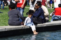 Families lounge by the fountain and a child dips a toe in the water to cool off. (Taneen Momeni/Bloc Reporter)